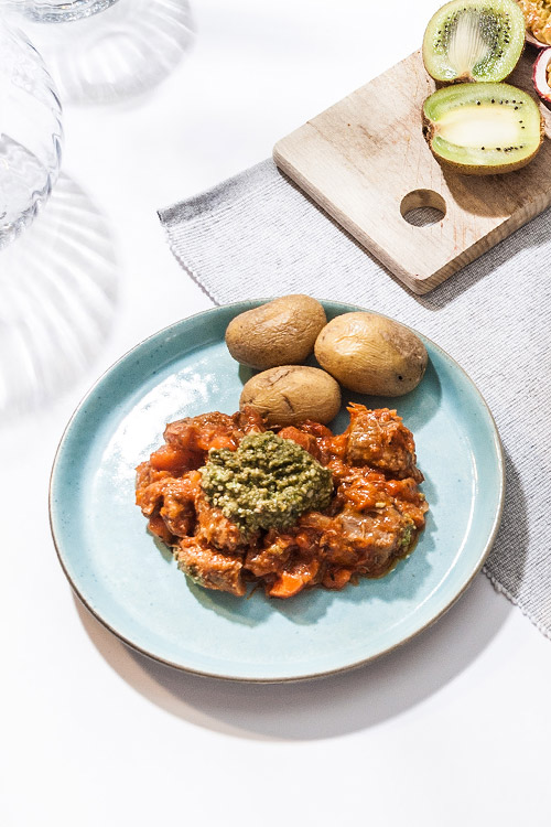 Osso buco på kalvkött med pesto serveras med kokt potatis.